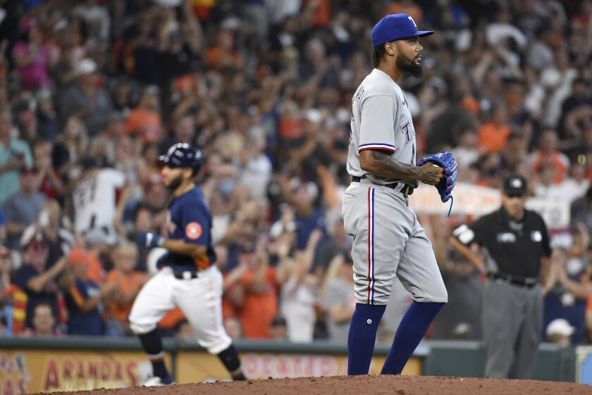 Texas Rangers starting pitcher Dennis Santana, right, walks away as Houston Astros' Abraham Toro, back left, rounds the bases after hitting a two-run home run during the fifth inning of a baseball game, Sunday, July 25, 2021, in Houston. (AP Photo/Eric Christian Smith)