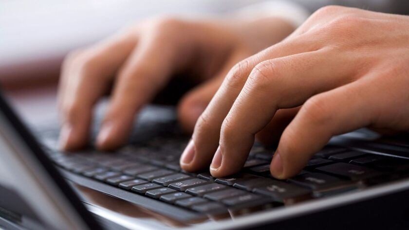 Close-up of male fingers typing a business document on the black laptop