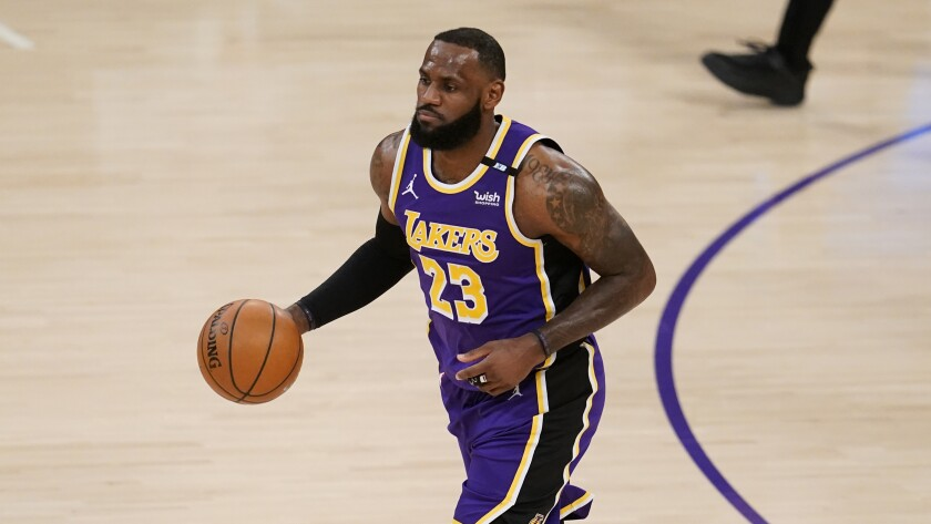 Los Angeles Lakers forward LeBron James dribbles during the first half of an NBA basketball game.