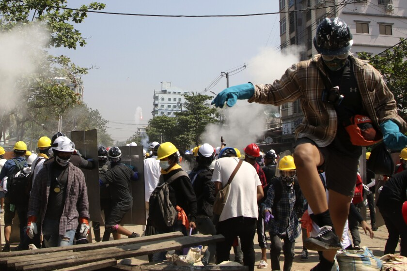 People in hard hats and masks gather in a street; some hold up metal shields.