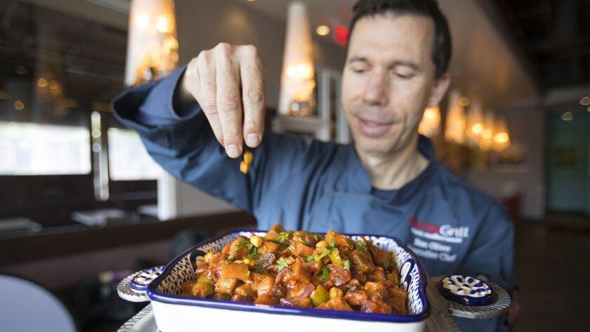 SAN DIEGO, CA 1/15/2019: Ron Oliver, executive chef at Luna Grill, finishes preparing Eggplant Tagin