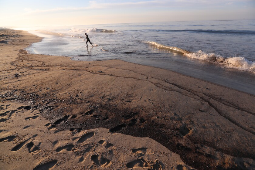 A person walks along the shore, marked by black lines of oil washing up from the ocean