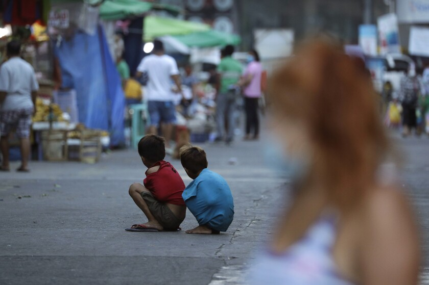 Niños en medio de la calle intentan utilizar sus camisetas para mantenerse calientes durante una cuarentena estricta, el miércoles 24 de marzo de 2021, en Manila, Filipinas. (AP Foto/Aaron Favila)