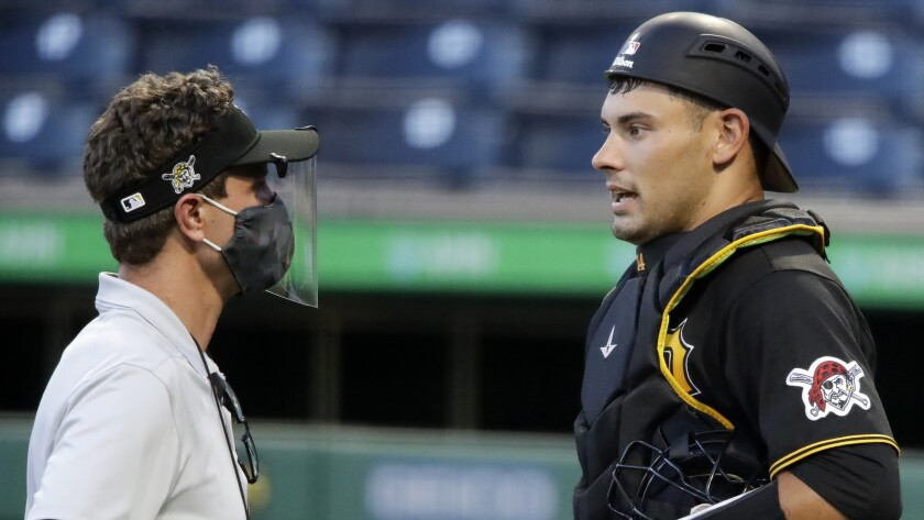 FILE - In this July 15, 2020, file photo, Pittsburgh Pirates catcher Luke Maile, right, talks with a trainer during an intrasquad baseball game at PNC Park in Pittsburgh. Maile underwent surgery to repair a fractured right index finger on Friday, July 17. The fracture was sustained after being by hit by a pitch in Thursday's intrasquad game at PNC Park. Maile is projected to resume competitive baseball activities in 10-12 weeks. (AP Photo/Gene J. Puskar, File)