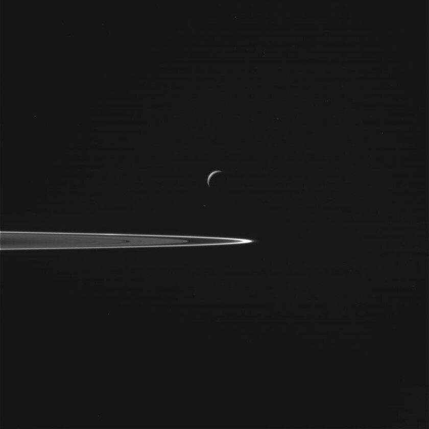 Enceladus appears to hover above Saturn's rings in this unprocessed image from NASA's Cassini spacecraft.