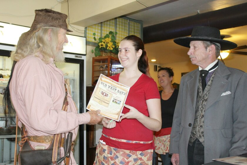Dressed as the historic characters they will play this weekend, Jim Cooper as a mountain man and Steve Johnson as Doc Holliday hand an Old West Days flyer to Kountry Kitchen waitress Brooke Elliott.