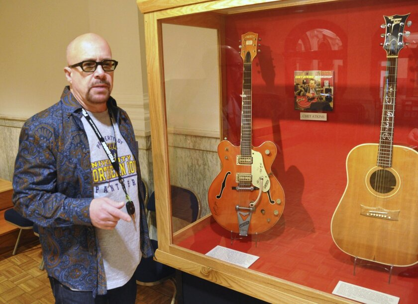 FILE - This April 22, 2013 file photo shows Memphis-based guitarist Robert Johnson standing by a display of guitars that belonged to Chet Atkins and Johnny Cash that he donated to the National Music Museum in Vermillion, S.D. Johnson also donated the guitar played by Elvis Presley during his final