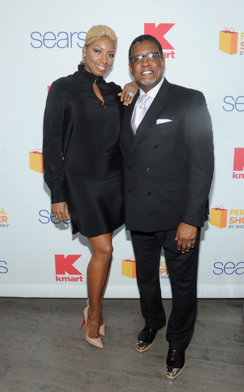A woman and man pose together in front of a backdrop at an event