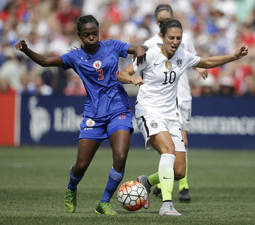 United States' Carli Lloyd, right and Haiti's Jennifer Limage fight for the ball in the first half during the US Women's World Cup victory tour, Sunday, Sept. 20, 2015, in Birmingham, Ala. (AP Photo/Brynn Anderson)