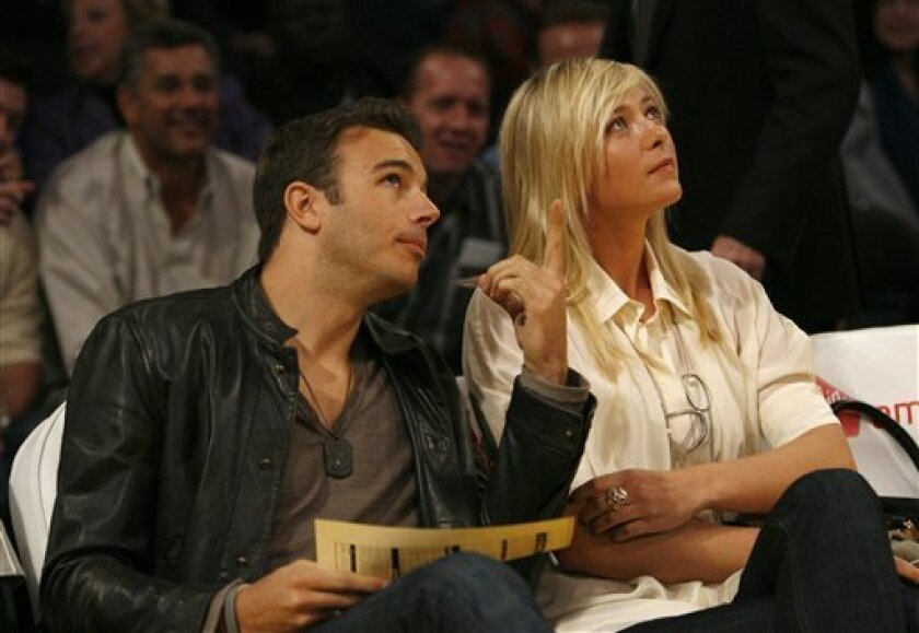 Tennis player Maria Sharapova, right, and Charlie Ebersol attend the NBA basketball game between the Los Angeles Lakers and the New Orleans Hornets at Staples Center in Los Angeles on Tuesday, Jan. 6, 2009. The Hornets won 116-105. (AP Photo/Danny Moloshok)