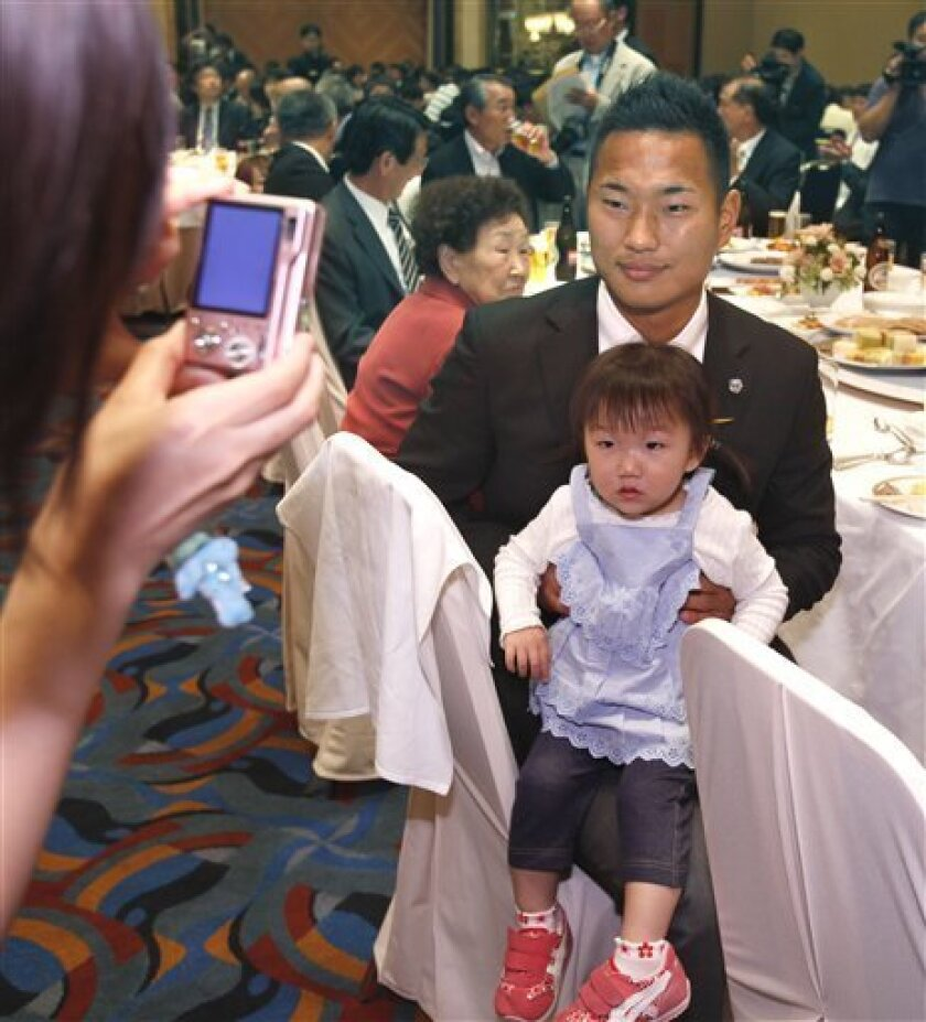 FILE - The May 16, 2010 file photo shows North Korean national team star striker Jong Tae Se posing with a girl for souvenir photos at a send-off party held by North Korean people living in Japan in Nagoya, central Japan. He plays like Rooney but behaves like Beckham. He loves his cars, his rap mus