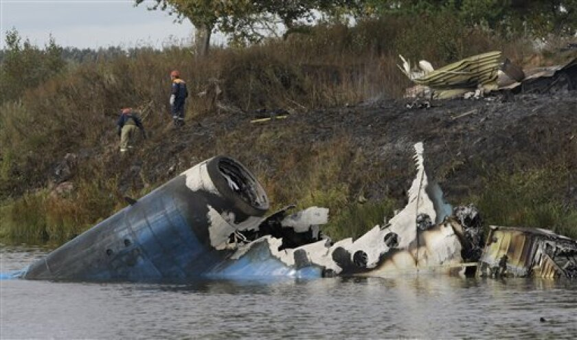 Rescuers seen at the crash site of Russian Yak-42 jet near the city of Yaroslavl, on the Volga River about 150 miles (240 kilometers) northeast of Moscow, Russia, Wednesday, Sept. 7, 2011. The Yak-42 jet carrying a top ice hockey team crashed while taking off Wednesday in western Russia. The Russian Emergency Situations Ministry said the plane was carrying the Lokomotiv ice hockey team from Yaroslavl. (AP Photo/Misha Japaridze)