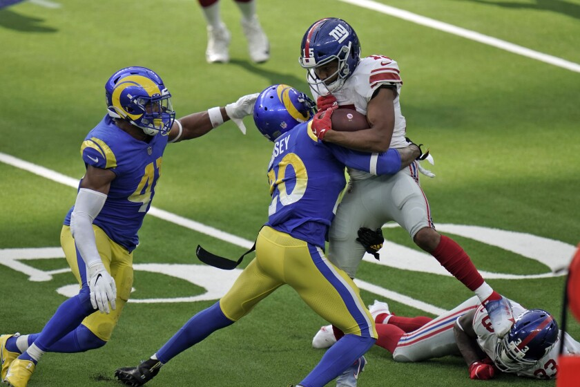 New York Giants wide receiver Golden Tate is tackled by Rams cornerback Jalen Ramsey.