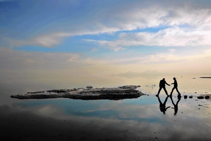 Two men walk toward salt-covered rocks that were once deep underwater at Lake Urmia, in northwestern Iran. Experts say that in the last two decades, a toxic combination of wasteful irrigation practices, the damming of feeder rivers, prolonged drought and a warming climate has accelerated the decline of the storied lake.