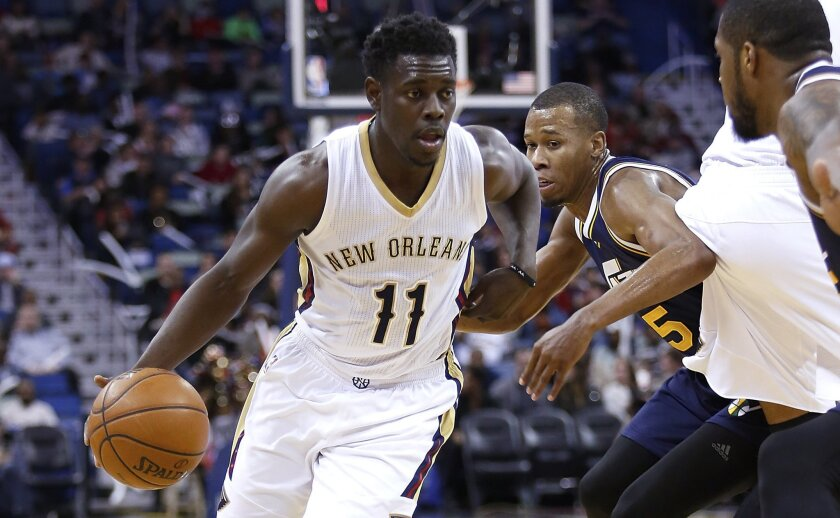 New Orleans Pelicans guard Jrue Holiday (11) drives past Utah Jazz guard Rodney Hood (5) during the first half of an NBA basketball game in New Orleans, Wednesday, Feb. 10, 2016. The Pelicans won 100-96. (AP Photo/Tyler Kaufman)