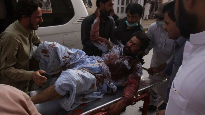 An injured man is rushed to a hospital in Quetta, Pakistan, on July 13, 2018, after a bombing at an election rally in Baluchistan province.