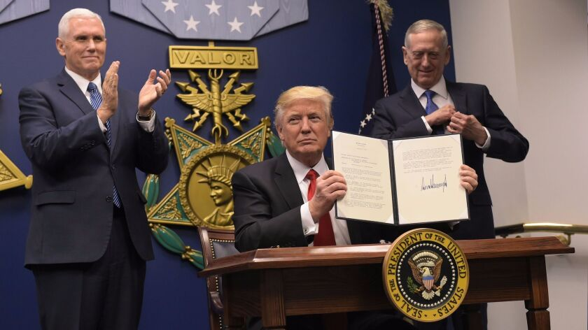 President Trump, flanked by Vice President Mike Pence, left, and Secretary of Defense James Mattis, shows his signature on executive orders signed Jan. 27. One of the orders banned people from seven predominantly Muslim nations from traveling to the United States.