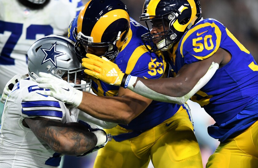 Rams defensive lineman Ndamukong Suh, left, and Samson Ebukam (50) stop Cowboys running back Ezekiel Elliott during the third quarter of their divisional round playoff game.