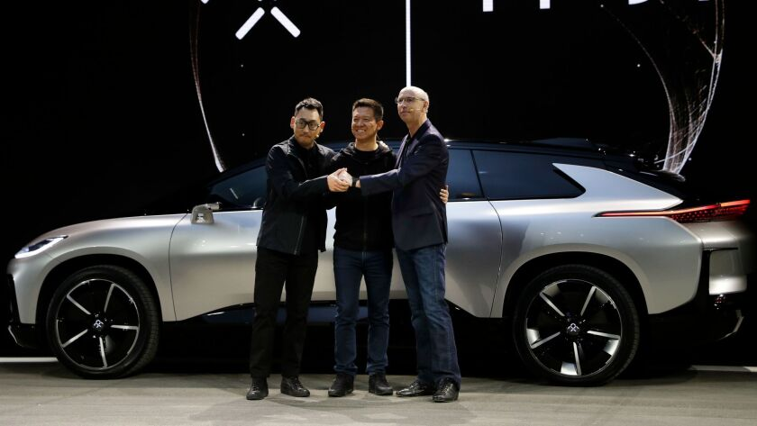 Chinese entrepreneur Jia Yueting, center, poses with Faraday Future executives Richard Kim, left, and Nick Sampson in January 2017. Kim has since left the company.