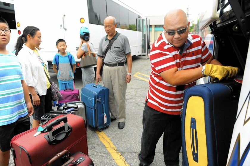 Bus driver Ramoncito Batac helps load passengers' luggage for a trip to Yellowstone National Park and Mt. Rushmore from America Asia Travel Center in Monterey Park.