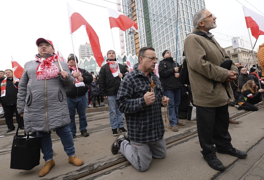 Men pray with rosaries before a march on Independence Day in Warsaw, Poland, Monday, Nov. 11, 2019. (AP Photo/Czarek Sokolowski)