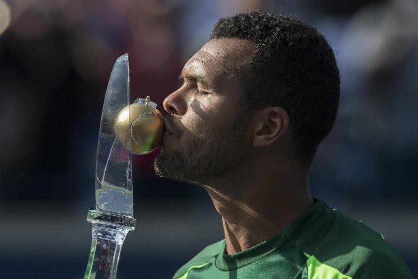France's Jo-Wilfried Tsonga kisses the trophy after beating Switzerland's Roger Federer 7-5, 7-6 to win the Men's Rogers Cup singles final in Toronto on Sunday, Aug. 10, 2014. (AP Photo/The Canadian Press, Chris Young)