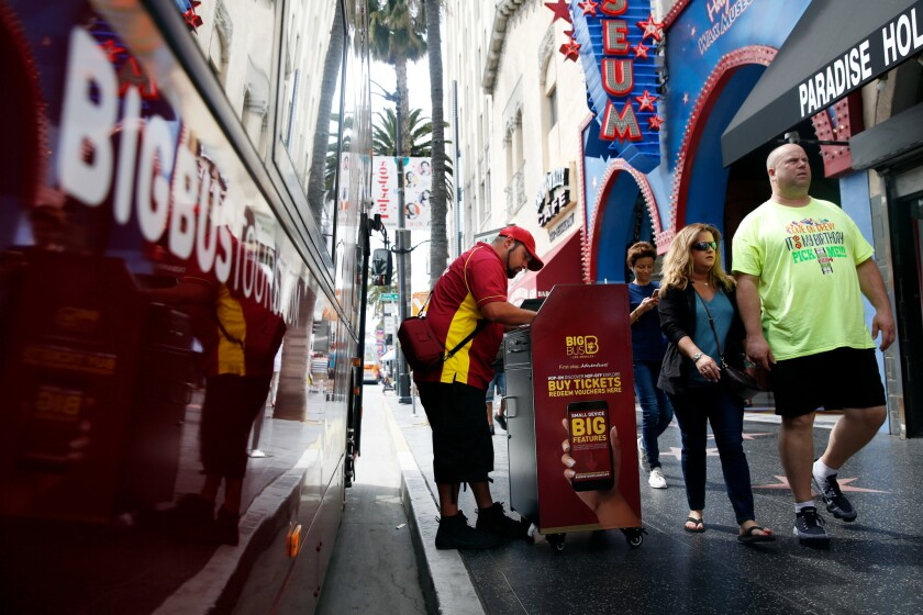 LOS ANGELES, CA-APRIL 8, 2019: People pass a Big Bus boarding area on Hollywood Blvd on April 8, 201