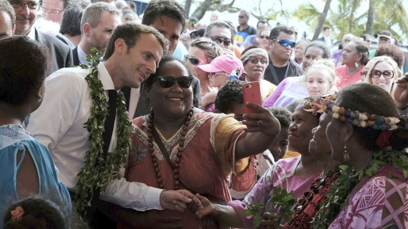 French President Emmanuel Macron poses for a selfie while meeting residents as part of a remembrance ceremony on Ouvea Island, in the archipelago of New Caledonia, in May. New Caledonia will vote on its independence from France on Sunday.