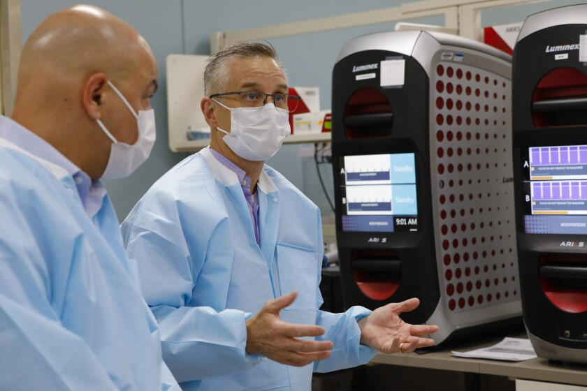Omid Bakhtar (l), M.D. a pathologist with Sharp Memorial Hospital and Aaron Harding (r), director of the Sharp Healthcare Laboratory point out some of the equipment used in the lab.