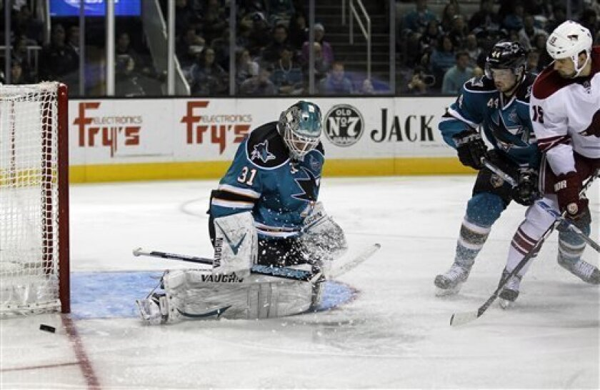 San Jose Sharks goalie Antti Niemi (31), of Finland, blocks a goal attempt by Phoenix Coyotes center Boyd Gordon (15) as San Jose Sharks defenseman Marc-Edouard Vlasic (44) defends during the second period of an NHL hockey game in San Jose, Calif., Saturday, March 30, 2013. (AP Photo/Tony Avelar)