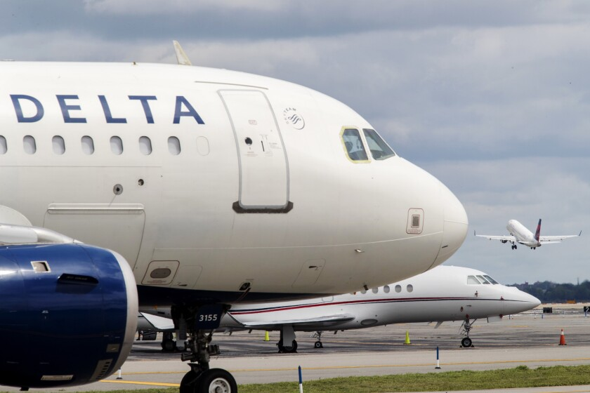 Delta jets on the tarmac at LaGuardia Airport as another takes off.