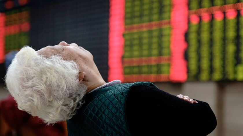 A woman takes a nap near displays of stock prices at a brokerage house in Shanghai, China, Friday, F