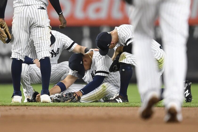 New York Yankees second baseman Gleyber Torres sits on the ground after slipping while trying to field a ground ball during the fourth inning of the team's baseball game against the Toronto Blue Jays, Friday, Sept. 20, 2019, in New York. (AP Photo/Sarah Stier)