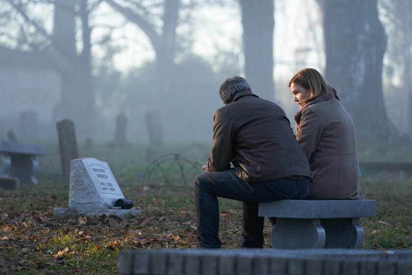 """View from behind of Ben Mendelsohn and Mare Winningham sitting on a stone bench in a cemetery in """"The Outsider."""""""