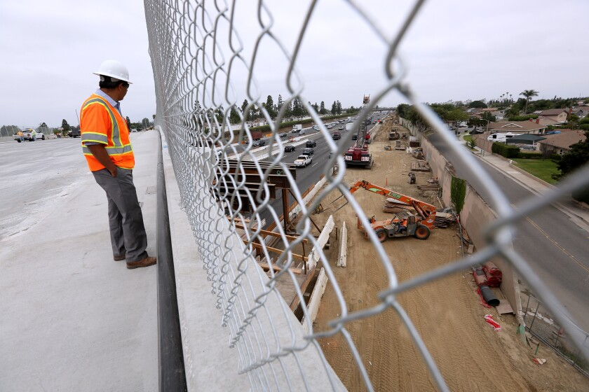 Wahed Ibrahim from OC 405 Partners looks over the freeway construction site while standing on the Slater Avenue bridge in Fountain Valley, which will reopen Thursday night. The bridge has four lanes, sidewalks and bike lanes on both sides.