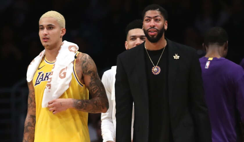 Anthony Davis, right, will miss his fourth consecutive game while recovering from a bruised gluteous maximus. Kyle Kuzma, left, has started in his place.