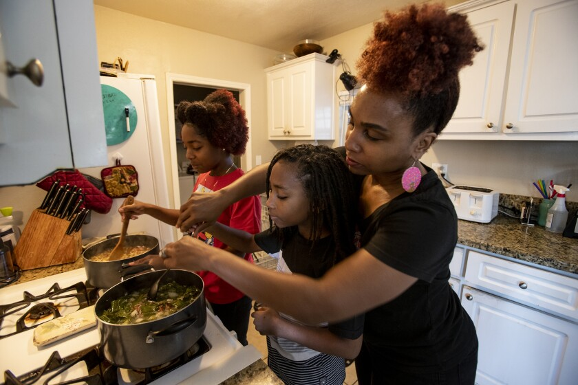 A mother and her children cook black eyed peas and collard greens