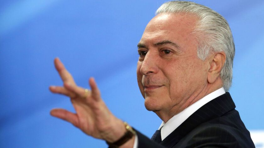 Brazilian President Michel Temer waves as he leaves a ceremony at the Planalto presidential palace in Brasilia on June 26, 2017.