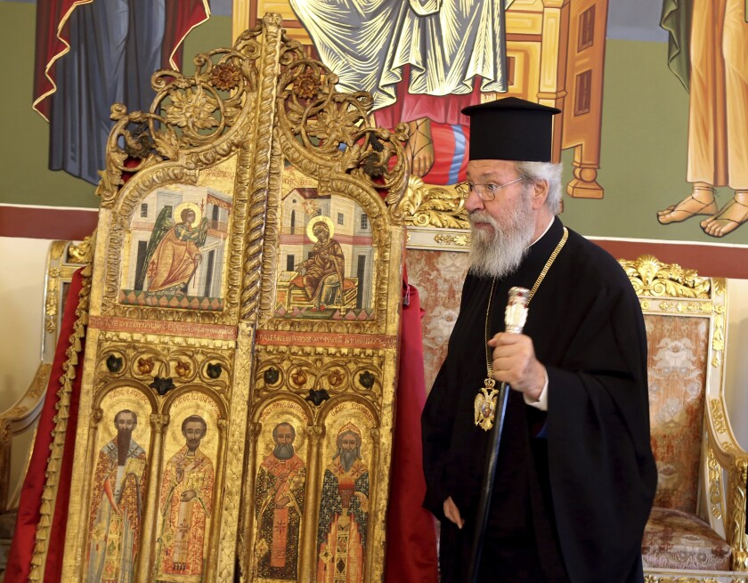 The leader of Cyprus Orthodox Church, Archbishop Chrysostomos II stands next to a pair of ornate, gilded doors that guard the altar of a church, at the Archbishopric in the capital Nicosia, on Thursday, Sept. 16, 2021 . The 18th century doors that were looted from the church of Saint Anastasios in the breakaway north of the ethnically divided island nation were repatriated from a Japanese art college after a long legal battle.(AP Photo/Philippos Christou)