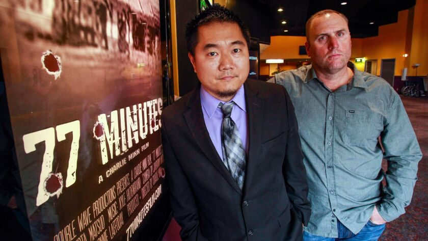 """Documentary film maker Charlie Minn, left, stands next to a movie poster for his film on the shooting massacre at the San Ysidro McDonalds in 1984, titled """"77 Minutes"""" with Josh Coleman, a victim of the shooting who was 11 at the time."""