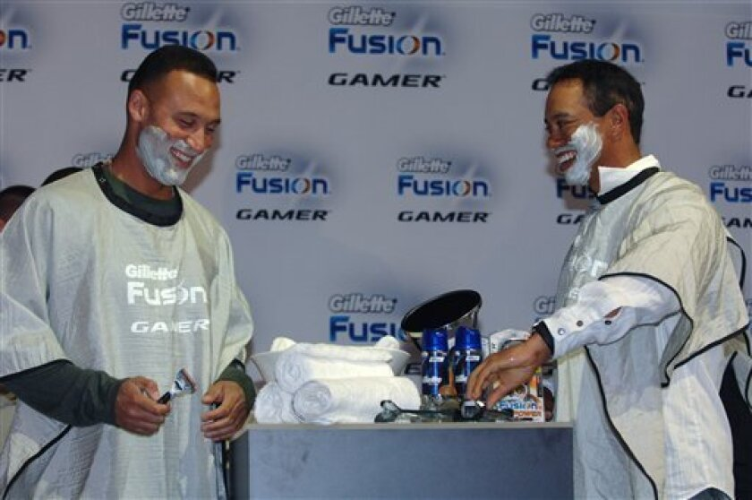 FILE - In this Feb. 3, 2009, file photo provided by Gillette, Gillette Champions New York Yankees' Derek Jeter, left, and golfer Tiger Woods help launch the Gillette Fusion Power Gamer razor during the Gillette-EA SPORTS Champions of Gaming Finals in Orlando, Fla. (AP Photo/Gillette, Phelan M. Ebenhack, File)