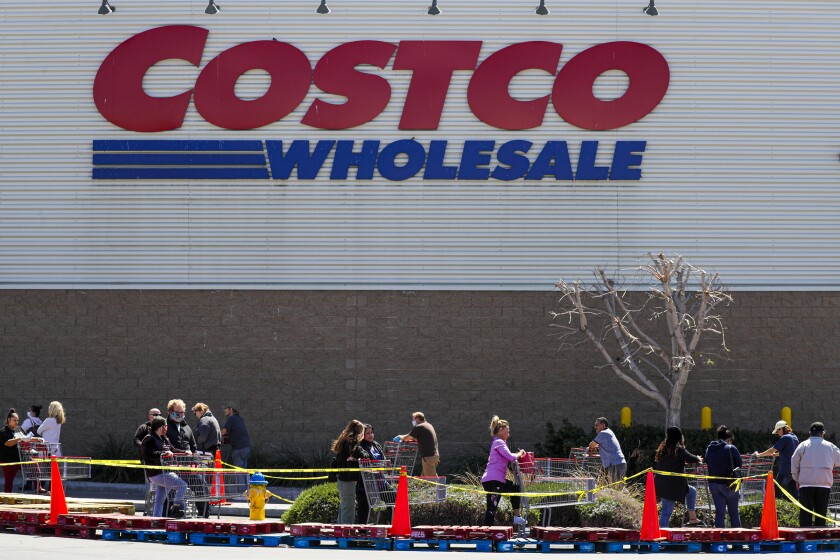 Shoppers line up Thursday outside a Costco in Victorville.
