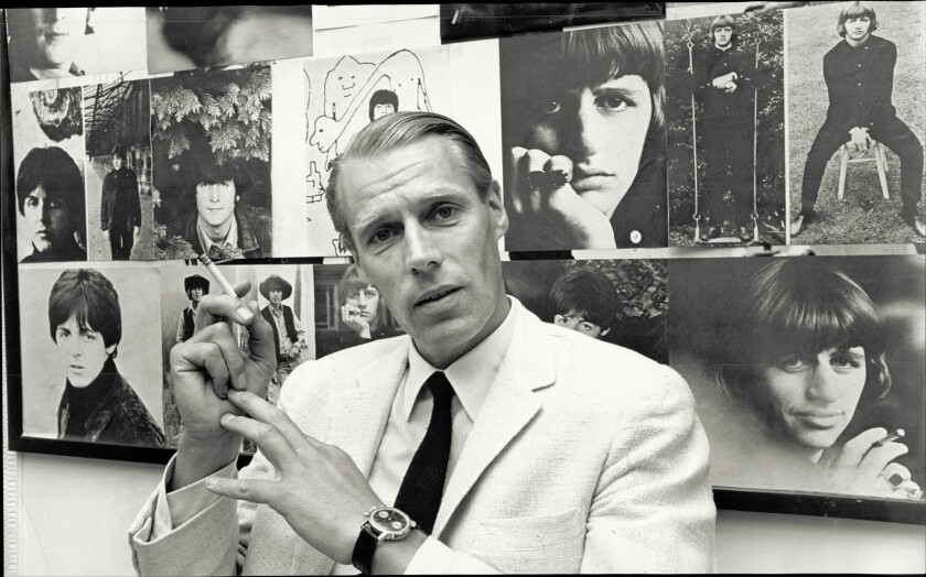 George Martin takes five before a backdrop of Beatles images — the band whose records he produced.