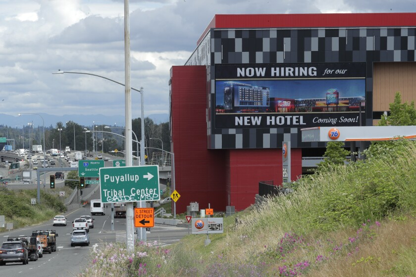 "A large video display reads ""Now hiring for our new hotel coming soon!"" in Tacoma, Wash."