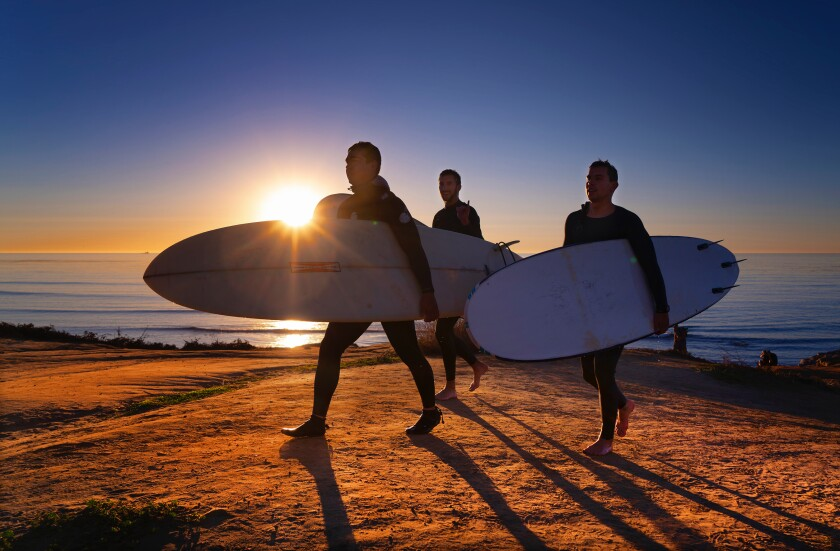 A small group of surfers return from surfing below the cliffs at Sunset Cliffs in Ocean Beach.