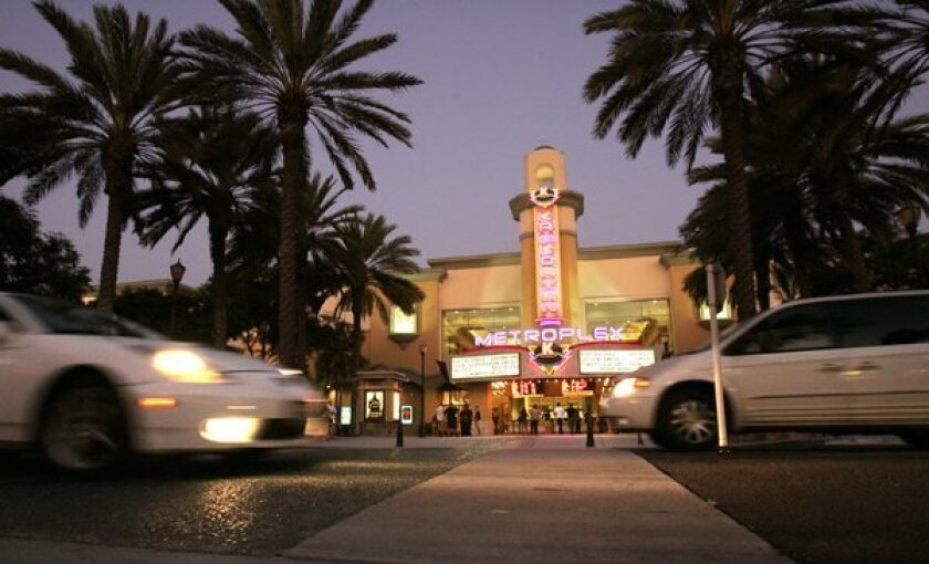 The brightly lit marquee of the Krikorian MetroPlex 15 theater lights up the Vista Village shopping center.