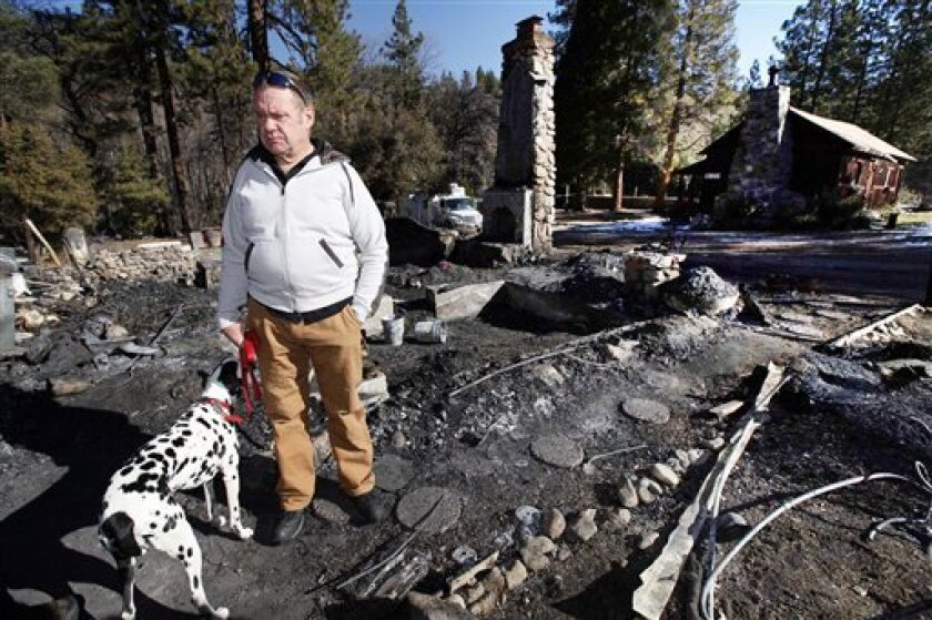 FILE - In this Friday, Feb. 15, 2013 file photo, Rick Heltebrake, with his dog Suni, looks over the burned-out cabin where Christopher Dorner's remains were found after a police standoff Tuesday near Big Bear, Calif. Dorner took his pickup during his escape attempt. Heltebrake, a ranger who takes c