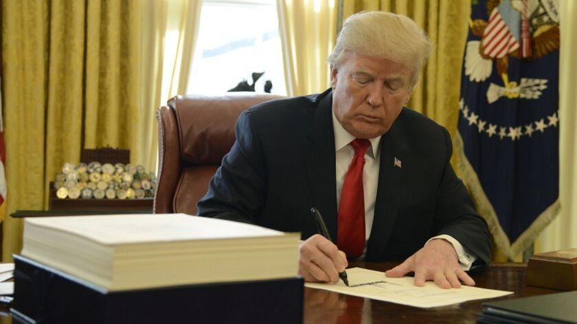 President Trump signs the $1.5-trillion tax cut bill in December.