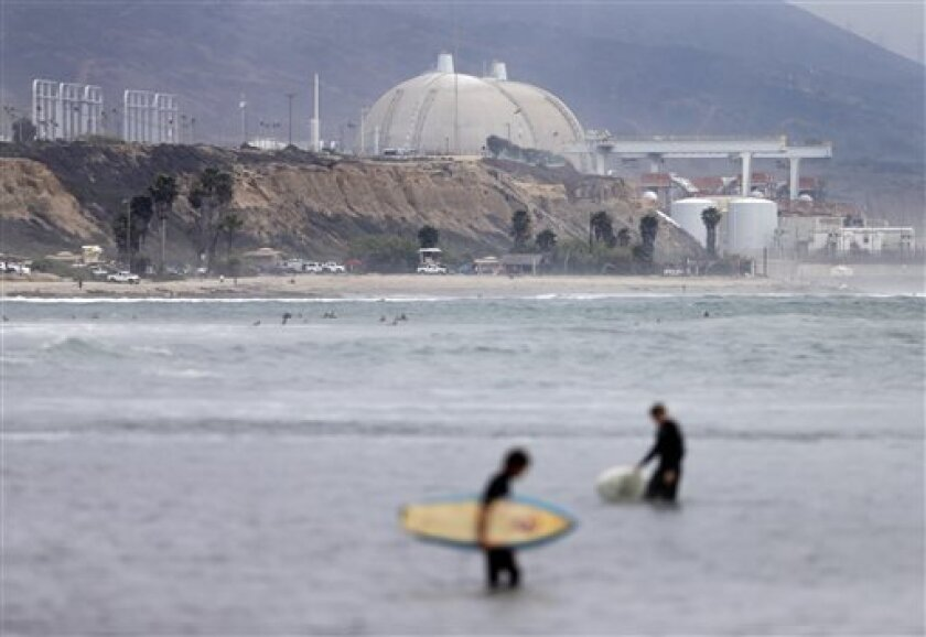 FILE - In this Friday, June 7, 2013 file photo, surfers pass in front of the San Onofre nuclear power plant in San Onofre, Calif. Southern California Edison says it is seeking to hold Mitsubishi Heavy Industries Ltd. and Mitsubishi Nuclear Energy Systems liable for defective steam generators that f