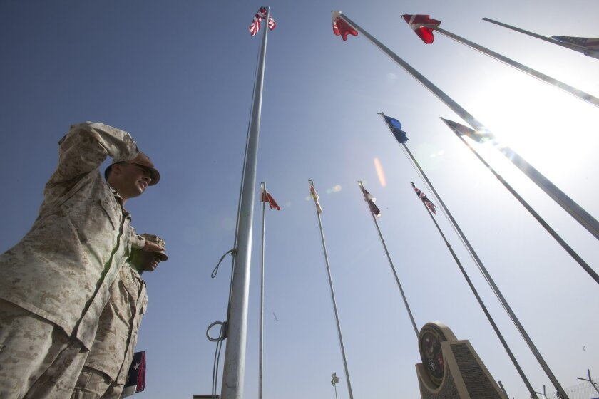 In 2011, Marines at Camp Leatherneck, Afghanistan salute 425 flags flown for troops in recognition of 9/11. (Photo by Petty Officer 1st Class Gino Flores/DOD)
